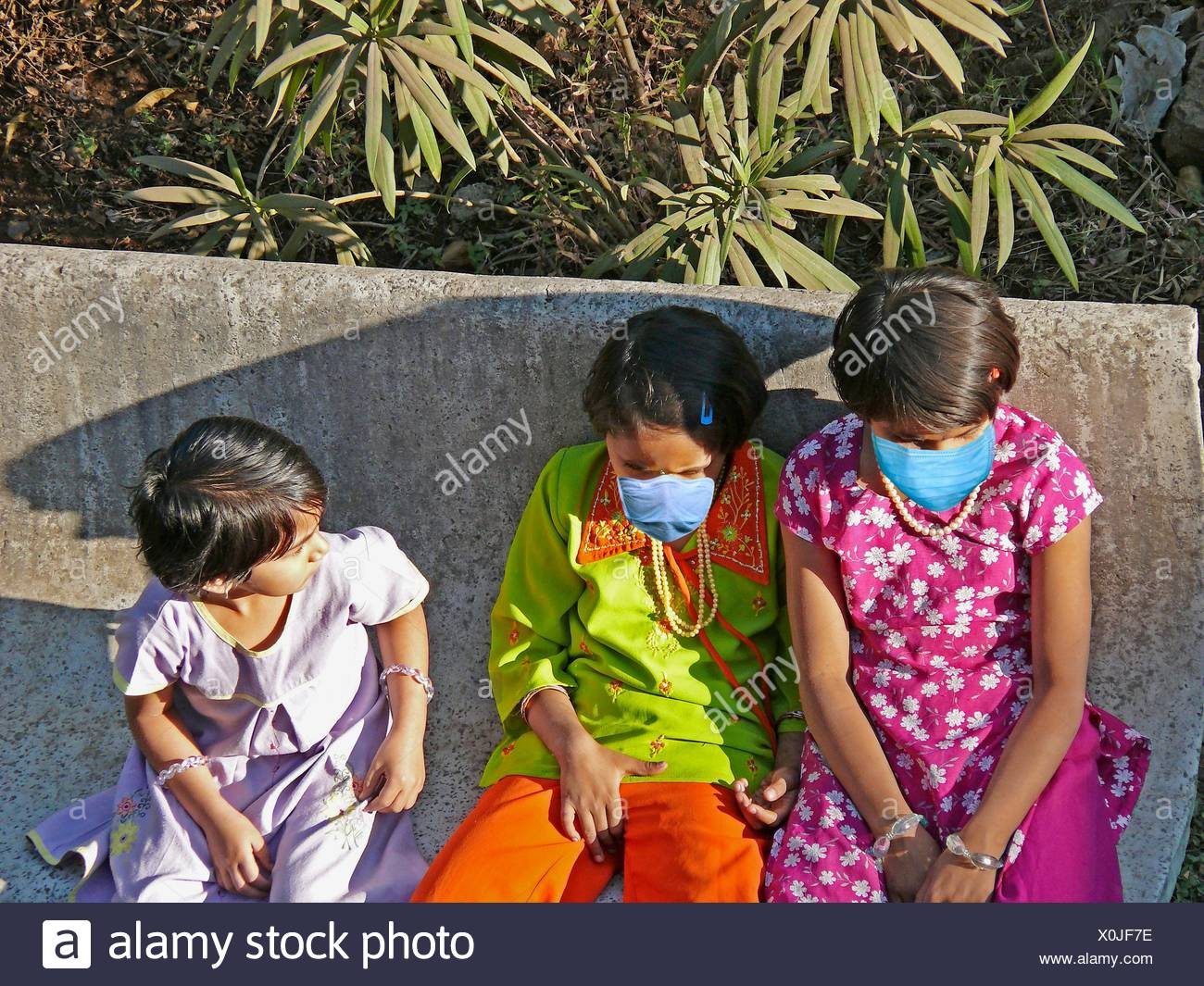 Small Girls in a garden with Precaution masks for Swine Flu, H1N1 - Stock Image