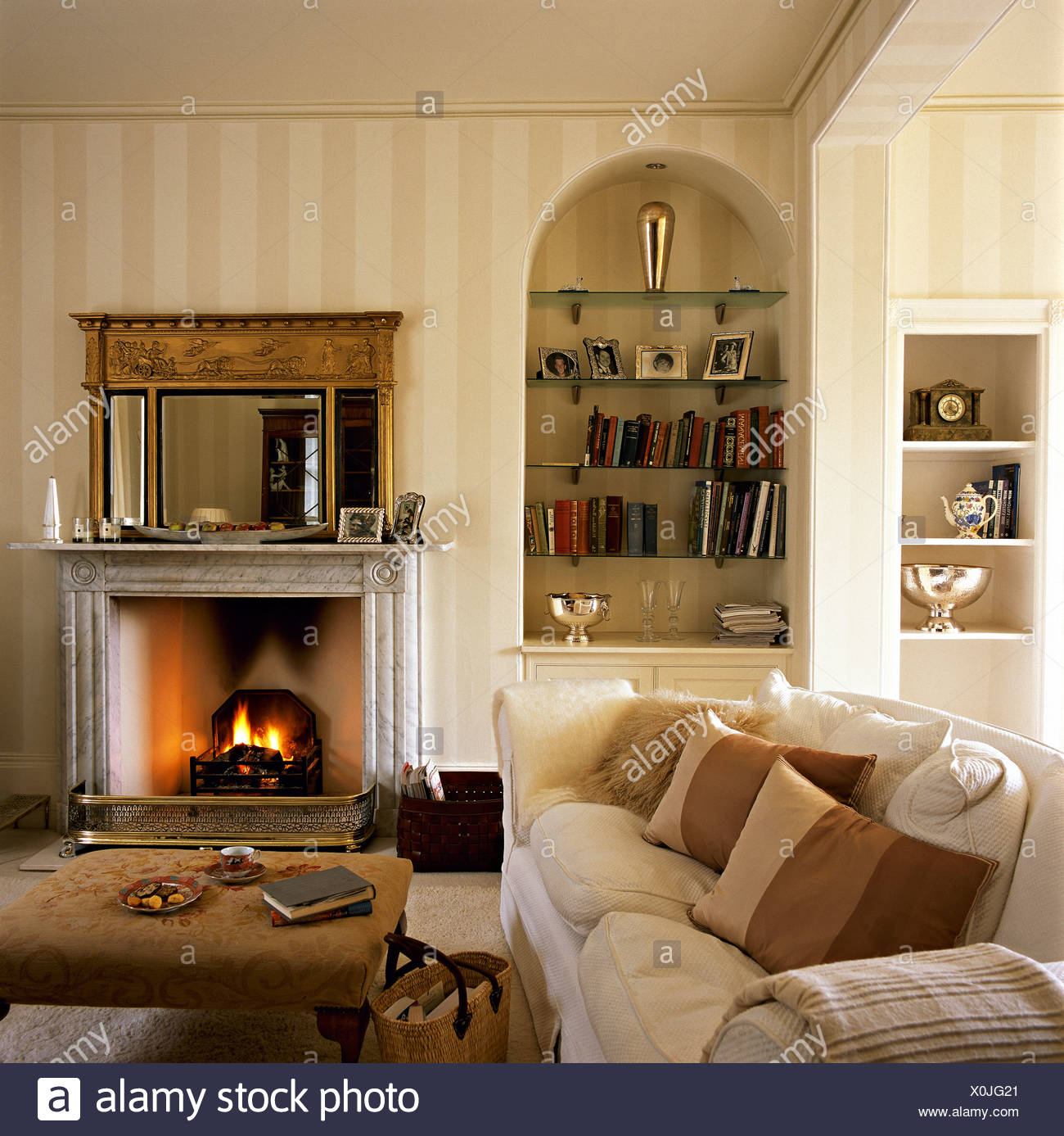Striped Cushions On Comfortable Cream Sofa Beside Upholstered Stool In  Country Living Room With Alcove Shelves Beside Fireplace