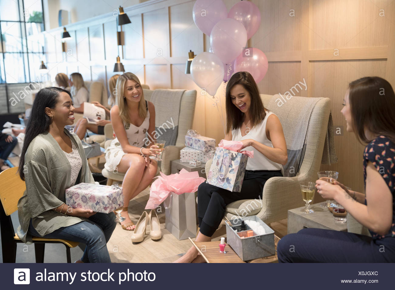 bride to be and bridesmaid friends opening gifts at bridal shower in nail salon