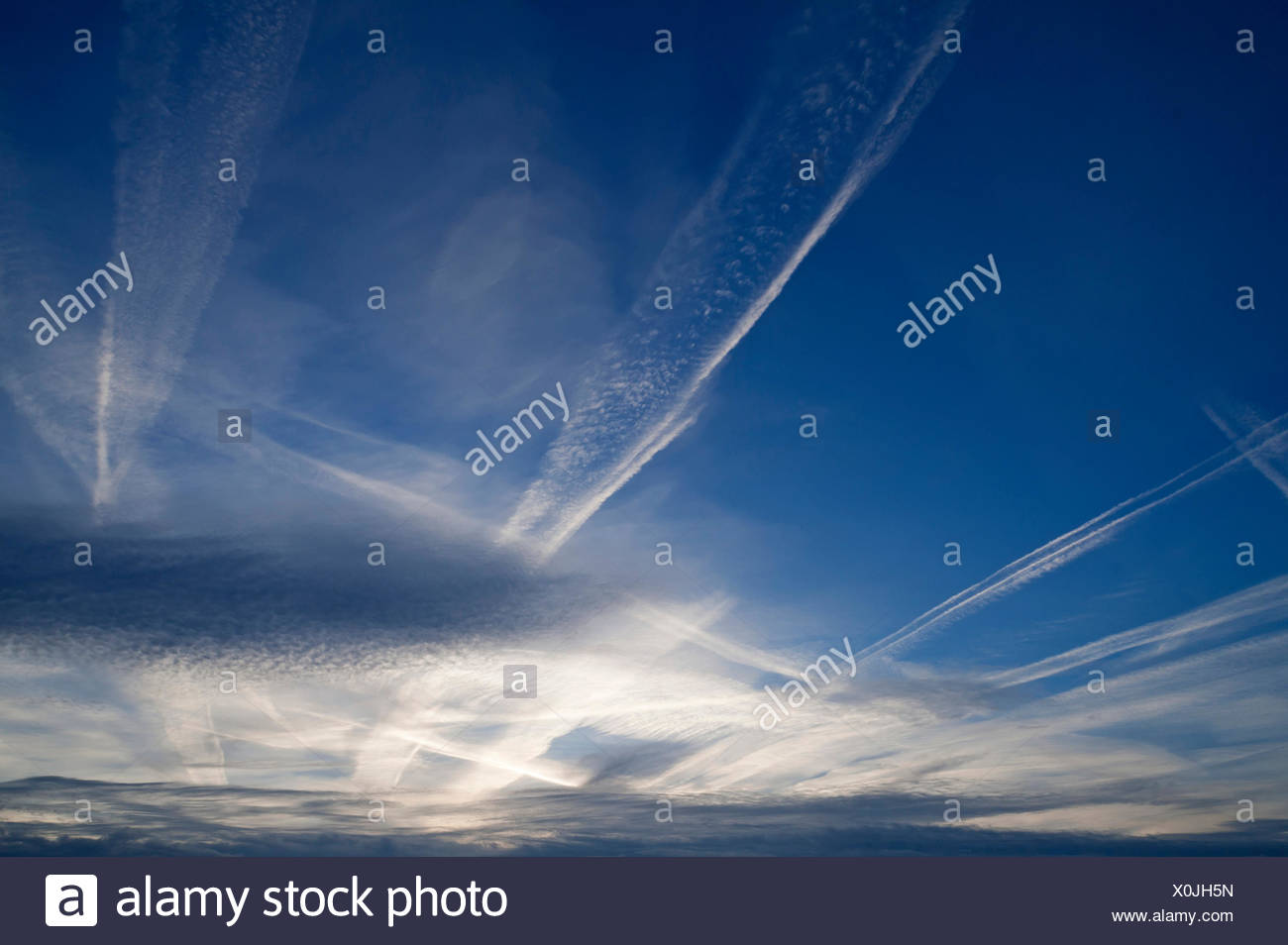 Small fluffy clouds, Cirrocumulus clouds, and medium-high stratus clouds, Altostratus, with contrails Stock Photo