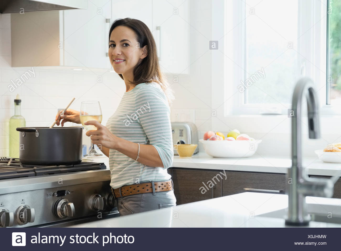 Portrait of smiling woman with wineglass cooking in kitchen - Stock Image
