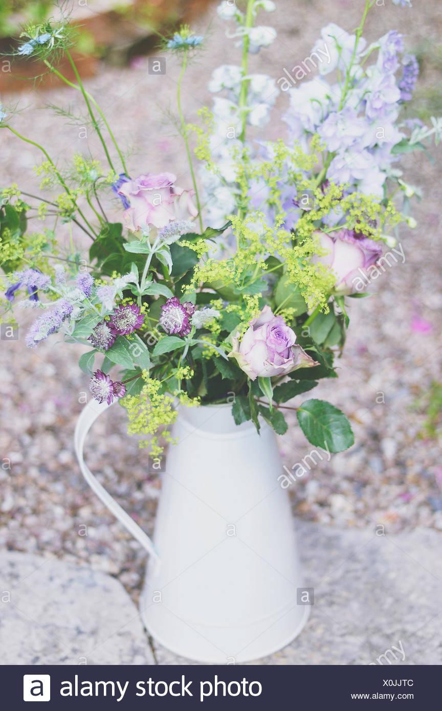 Purple flower arrangement in vintage milk jug - Stock Image