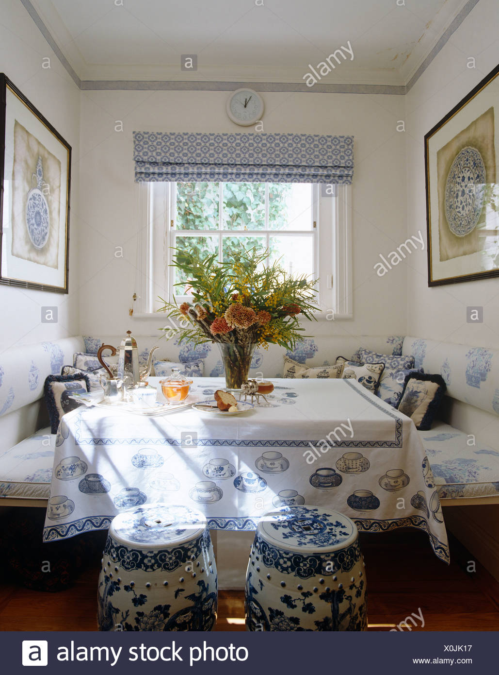 Blue+white Chinese pottery stools at table with teacup themed cloth and bench seating with blue+white cushions Stock Photo