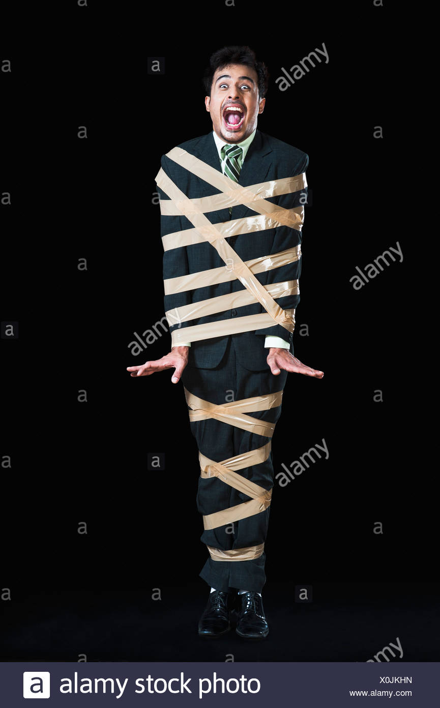 Businessman tied up with adhesive tape and looking frustrated - Stock Image