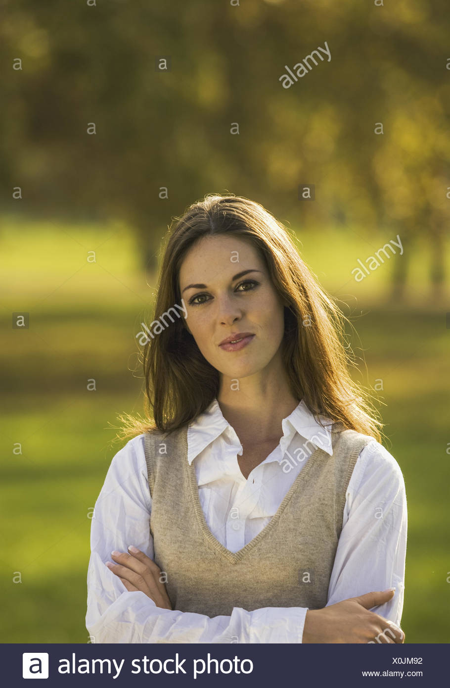 Frau in herbstlichem Park, verschraenkte Arme, Halbportraet (model-released) Stock Photo