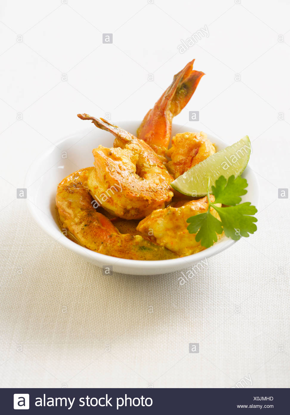 King prawns in curry marinade with lemon slices on plate - Stock Image
