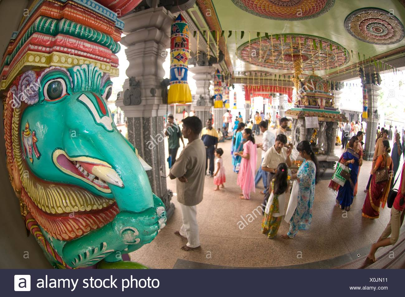 Devotees and gaudy elephant painted column during Deepavali ceremony, Sri Veeramakaliamman Temple, Little India, Singapore. - Stock Image