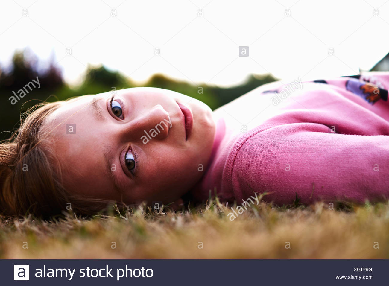 Close up portrait of a girl lying on grass - Stock Image