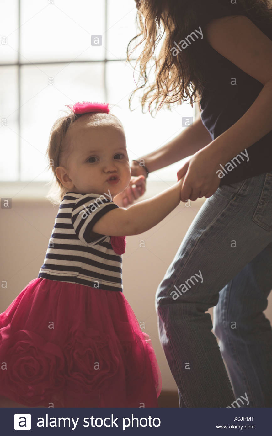 Female toddler dancing with sister in living room - Stock Image