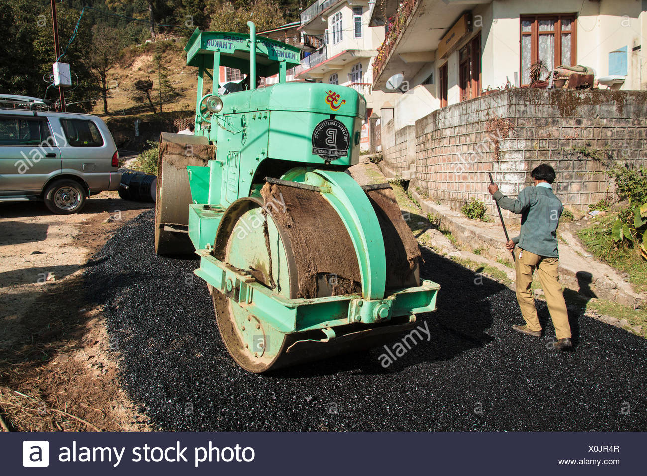 Road construction workers laying tar, roller rolls over fresh asphalt, Tota Rani, Dharamsala, Himal Pradesh, India - Stock Image