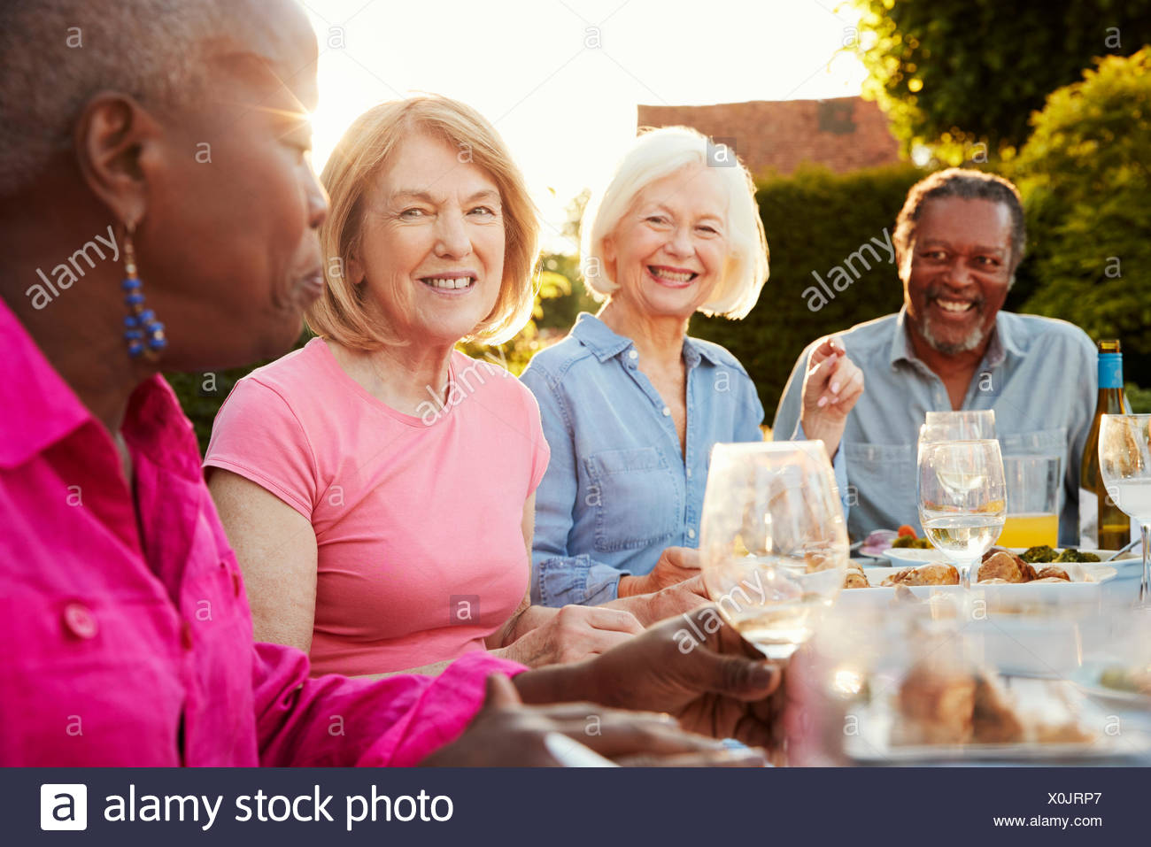 Group Of Senior Friends Enjoying Outdoor Dinner Party At Home - Stock Image