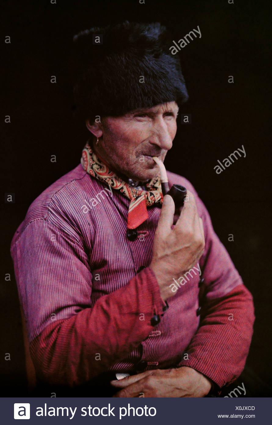 A Dutch man wears a bearskin cap and smokes a pipe Stock