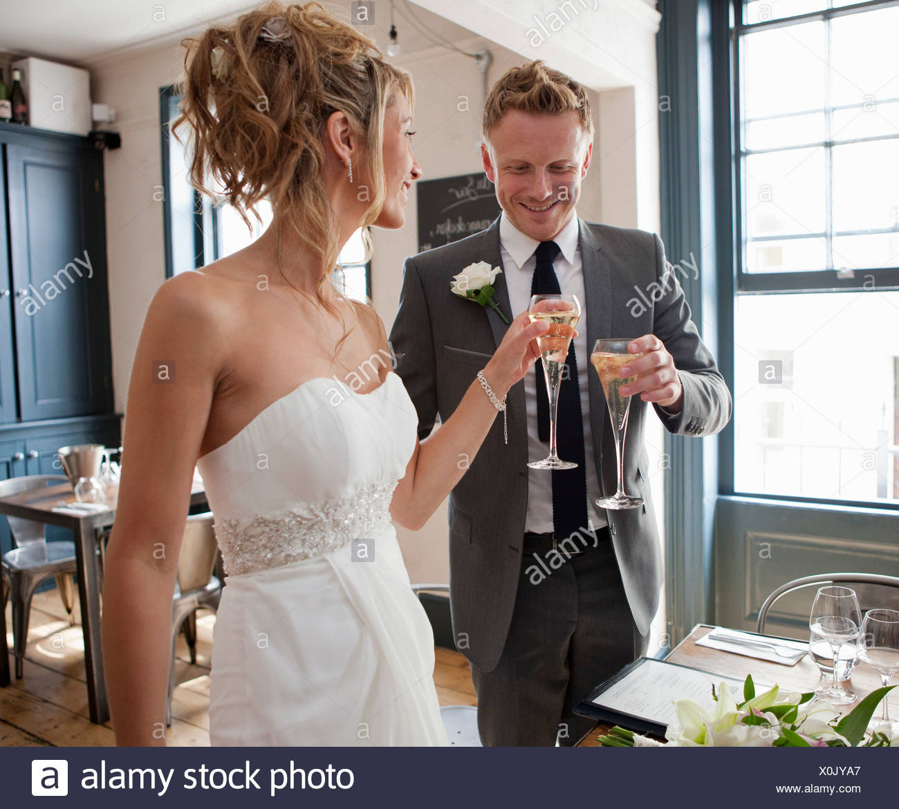 Bride and groom toasting with champagne at wedding ceremony - Stock Image