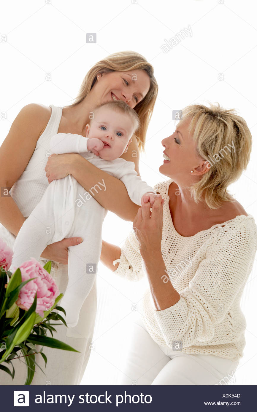 Mother holding baby, grandmother smiling - Stock Image