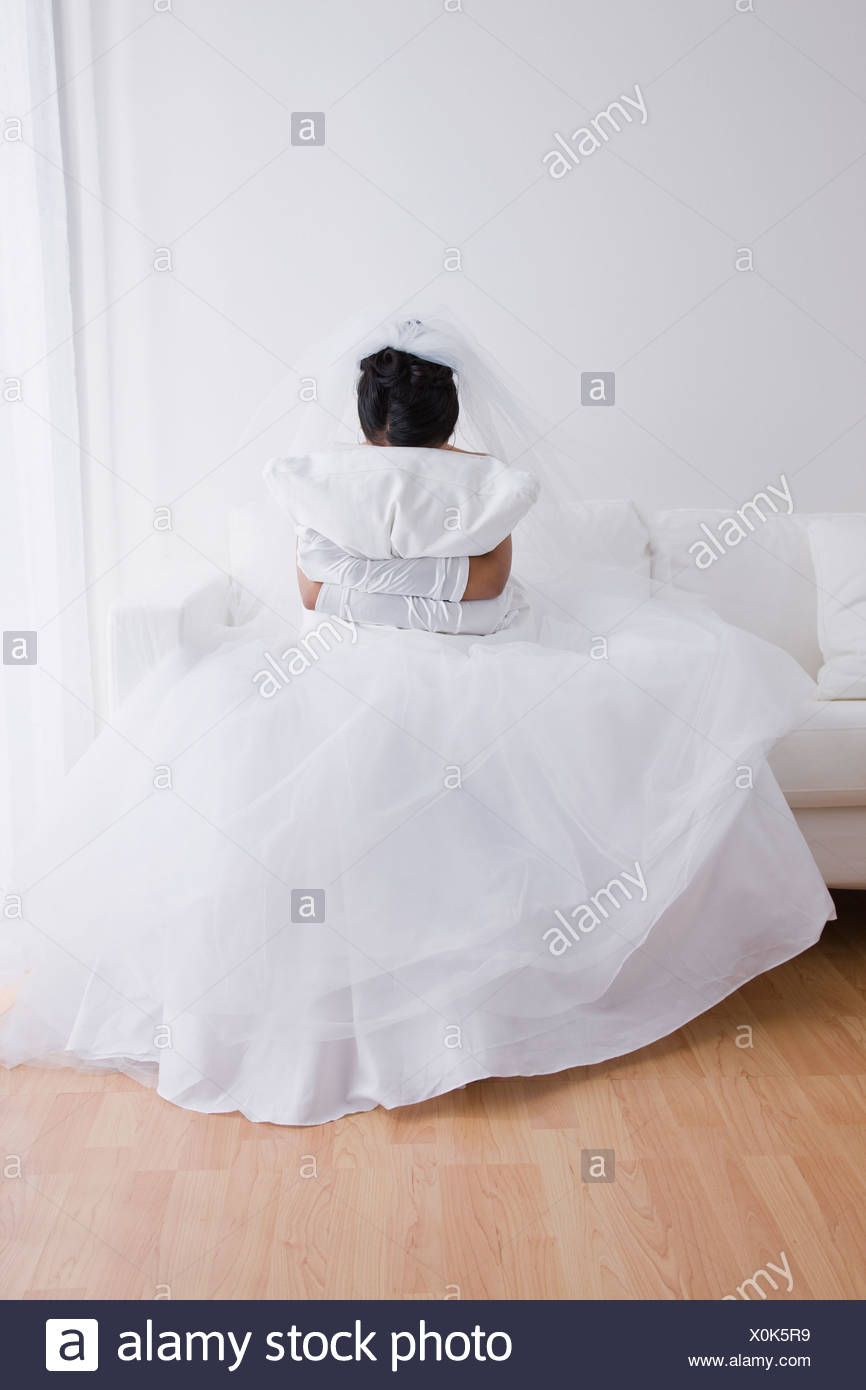 Bride crying on couch and hugging pillow - Stock Image