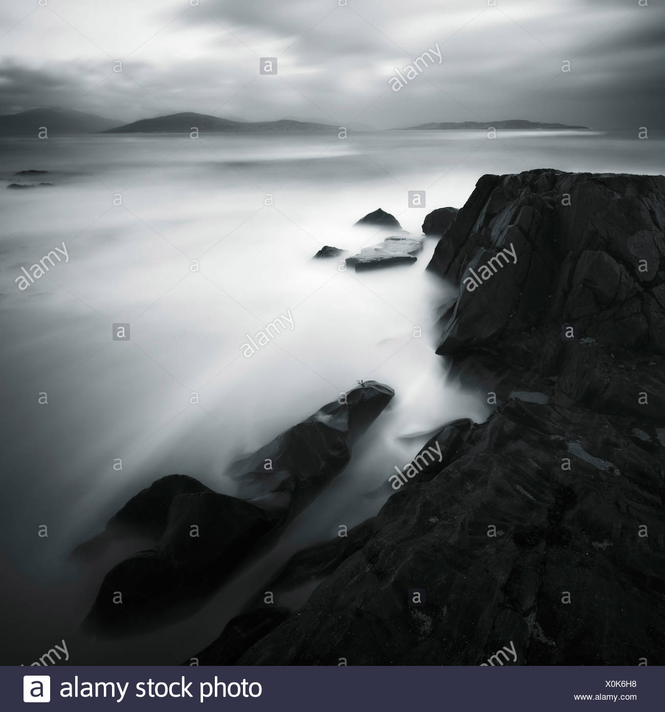 Moving water and black rocks - Stock Image