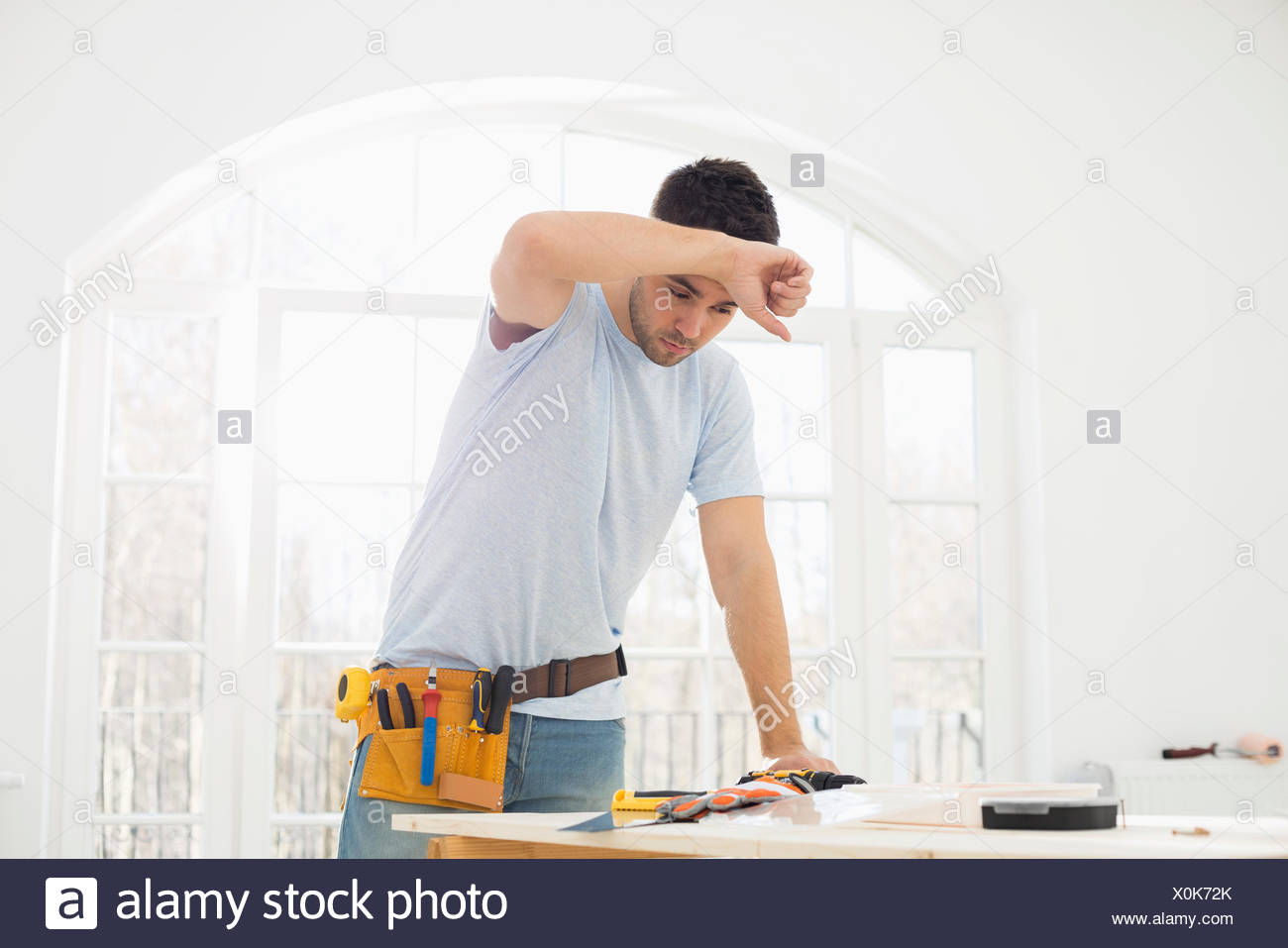 Mid-adult carpenter wiping his brow in new house - Stock Image