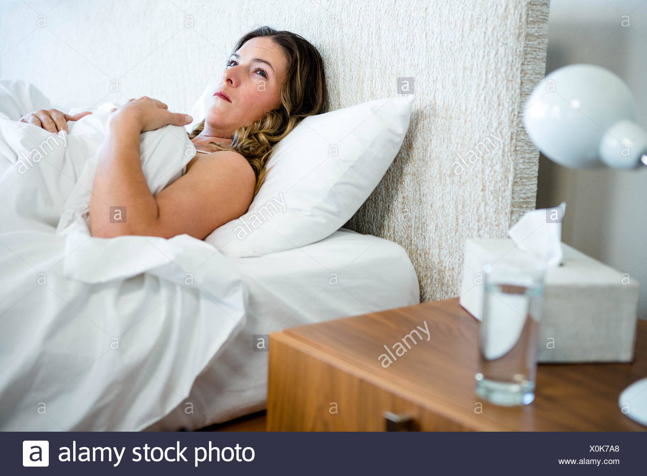 sick woman lying in her bed - Stock Image
