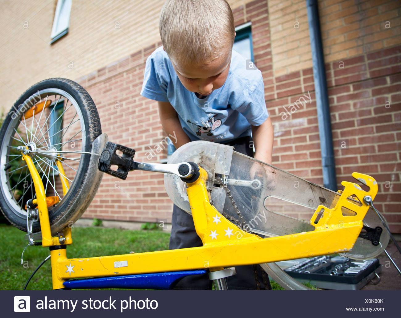 Boy repairing cycle - Stock Image