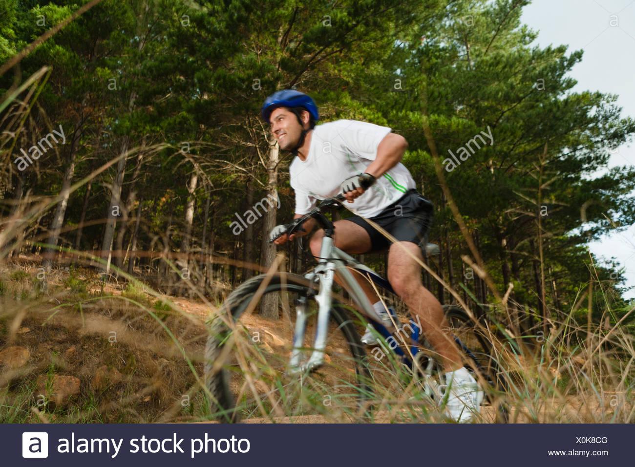 Man mountain biking on dirt path - Stock Image