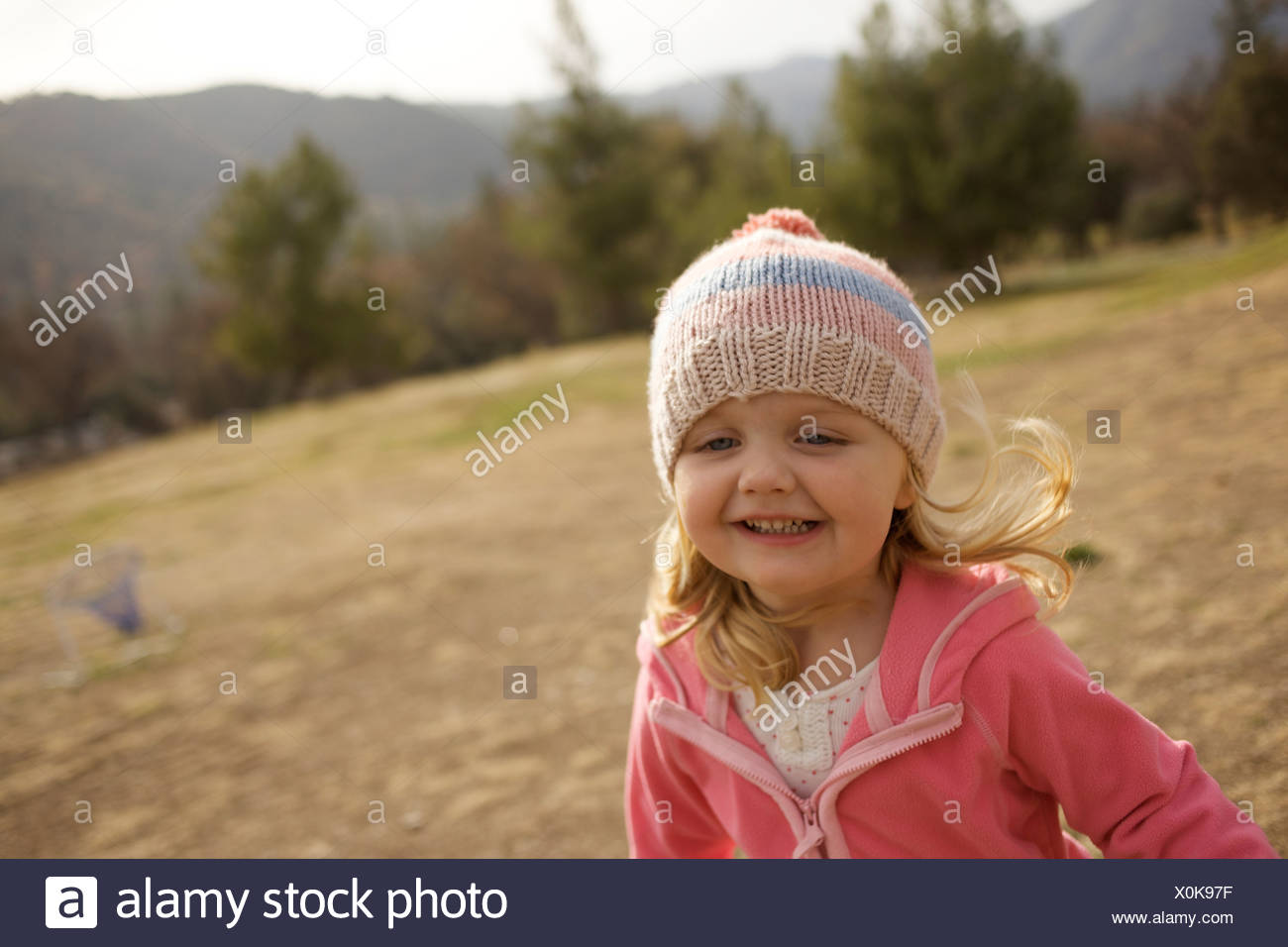 Young girl runs and smiles. - Stock Image