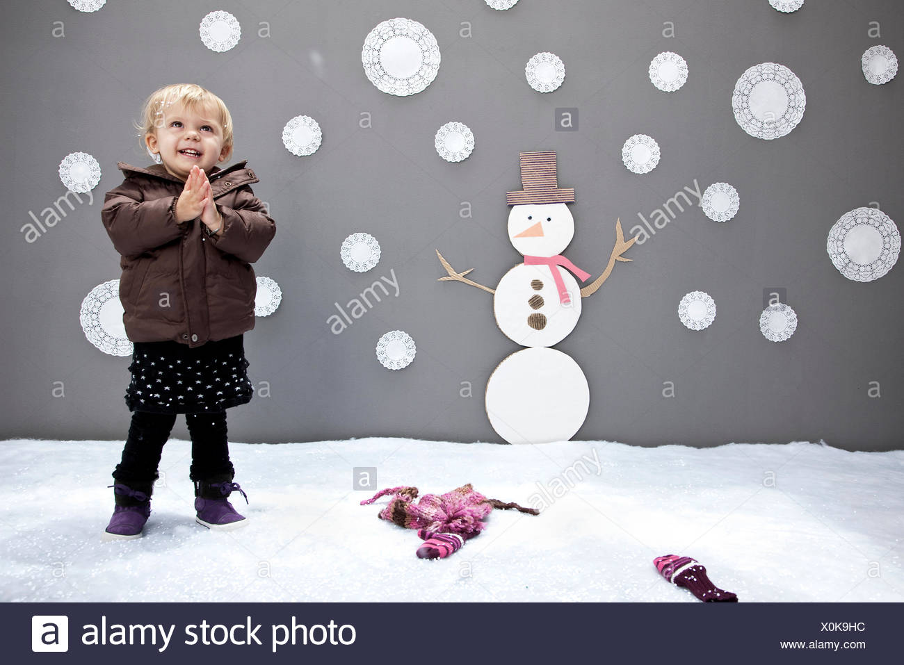Baby girl with snowman and snowflake cutouts - Stock Image