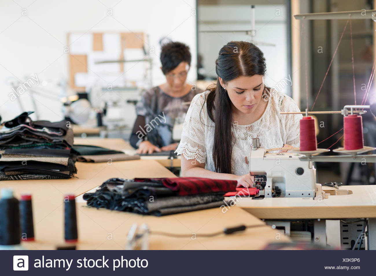 Two seamstresses using sewing machines in workshop - Stock Image
