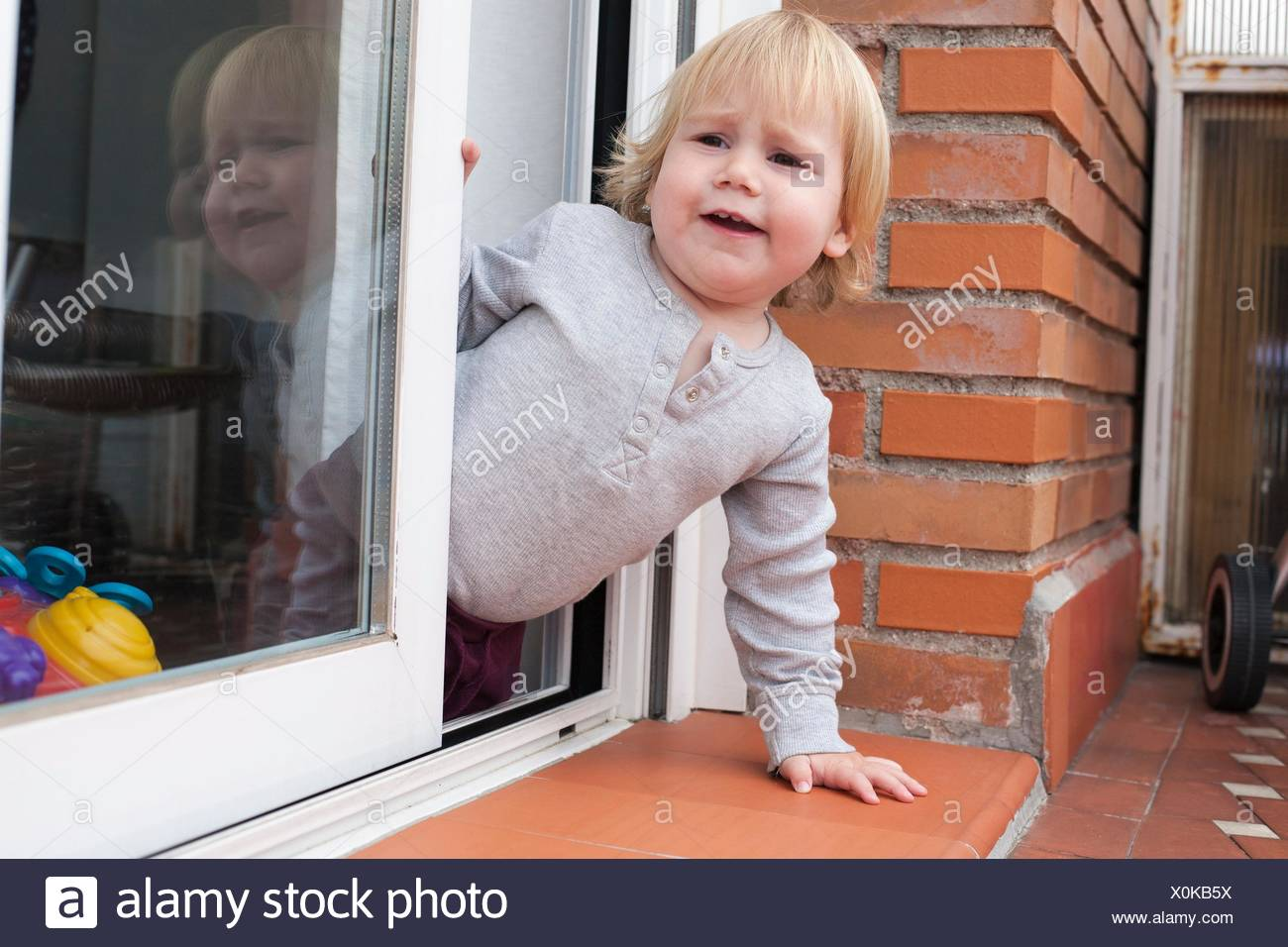portrait of blonde caucasian baby nineteen month age chubby face calling peering terrace floor supported on the arms. - Stock Image