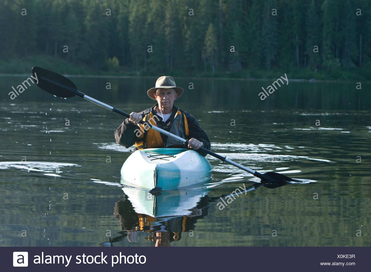 Retired man kayaking in Idaho. - Stock Image