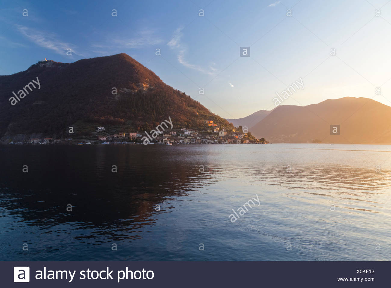 Monte Isola reflection on Lake Iseo during a winter sunset, Brescia Province, Iseo Lake, Lombardy, Italy. - Stock Image