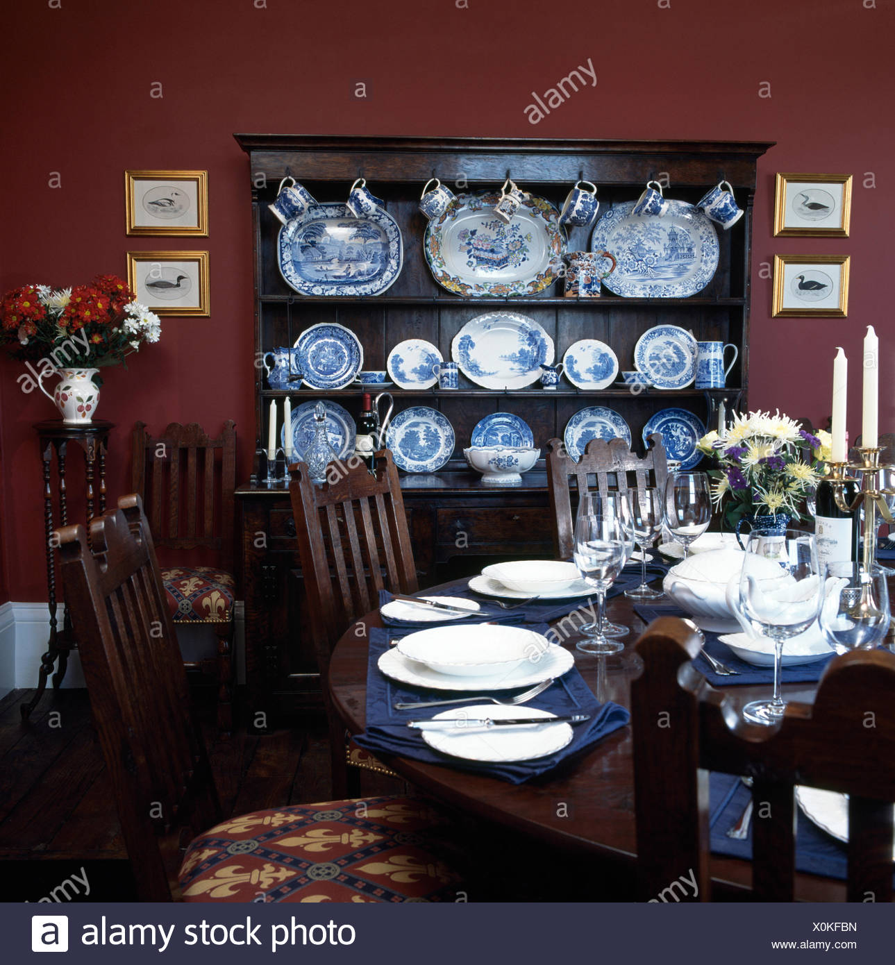 Table Set For Dinner In Dark Red Nineties Dining Room With A Collection Of Blue
