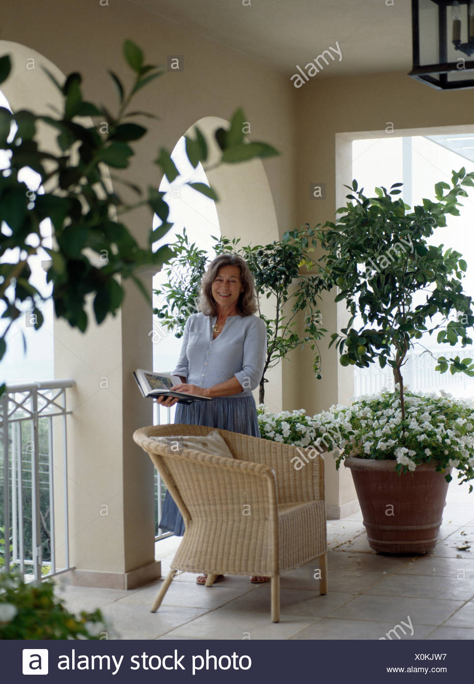 Portrait of woman standing on veranda of French house         FOR EDITORIAL USE ONLY - Stock Image