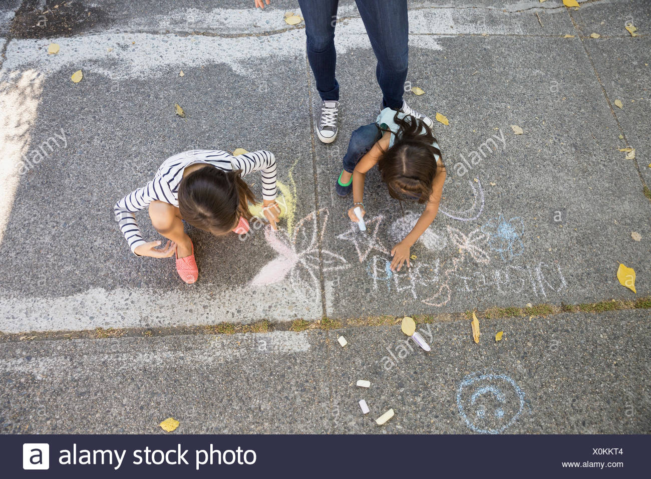 Sisters drawing with sidewalk chalk - Stock Image