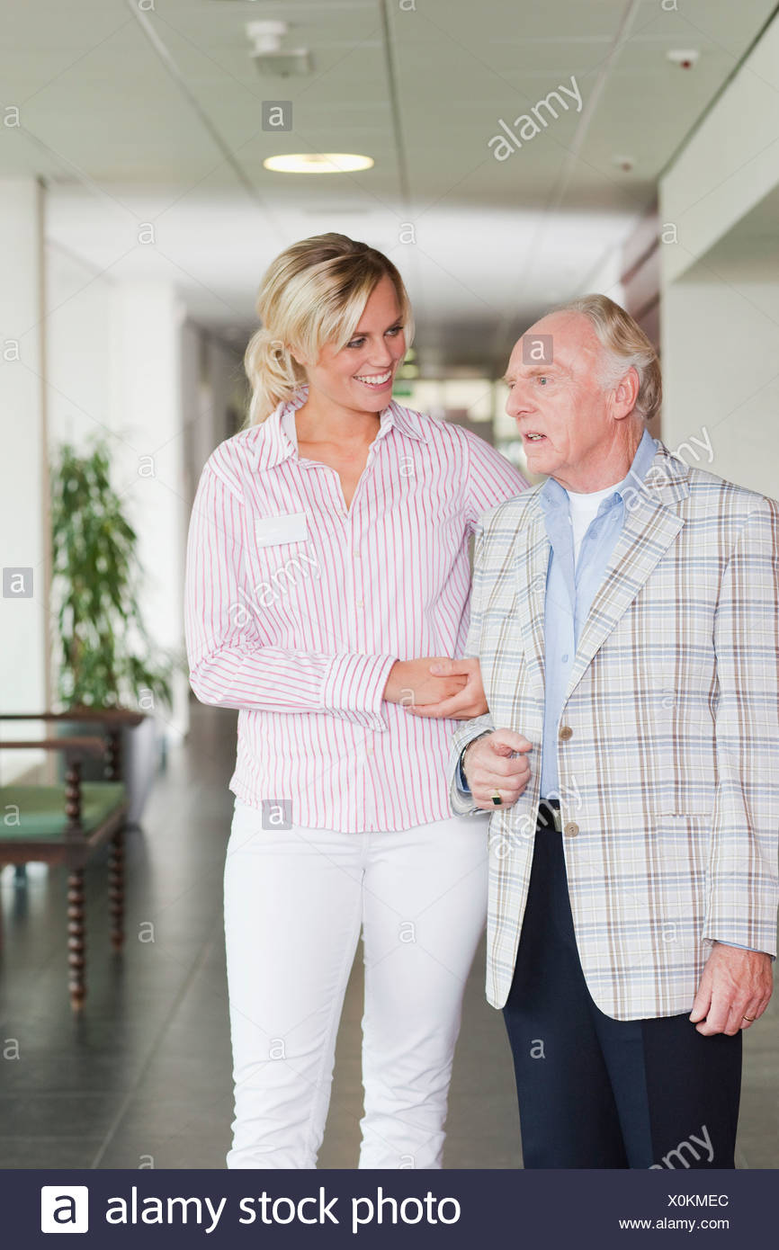 A senior man talking to a care assistant in a retirement home - Stock Image