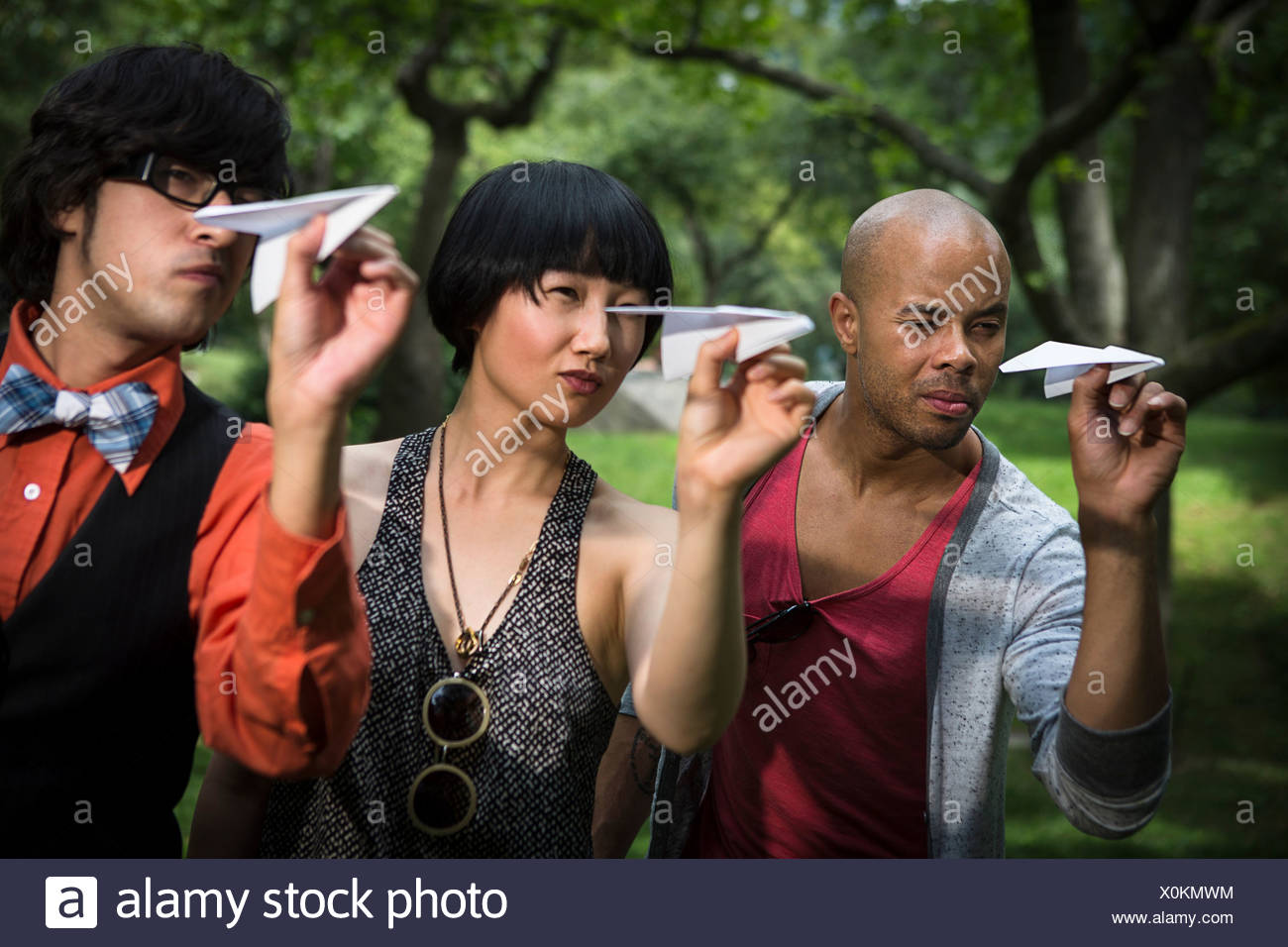 Three friends throwing paper planes in park Stock Photo
