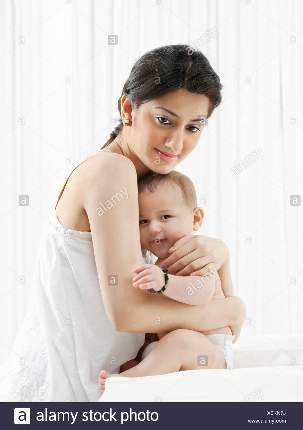 Mother hugging her baby - Stock Image