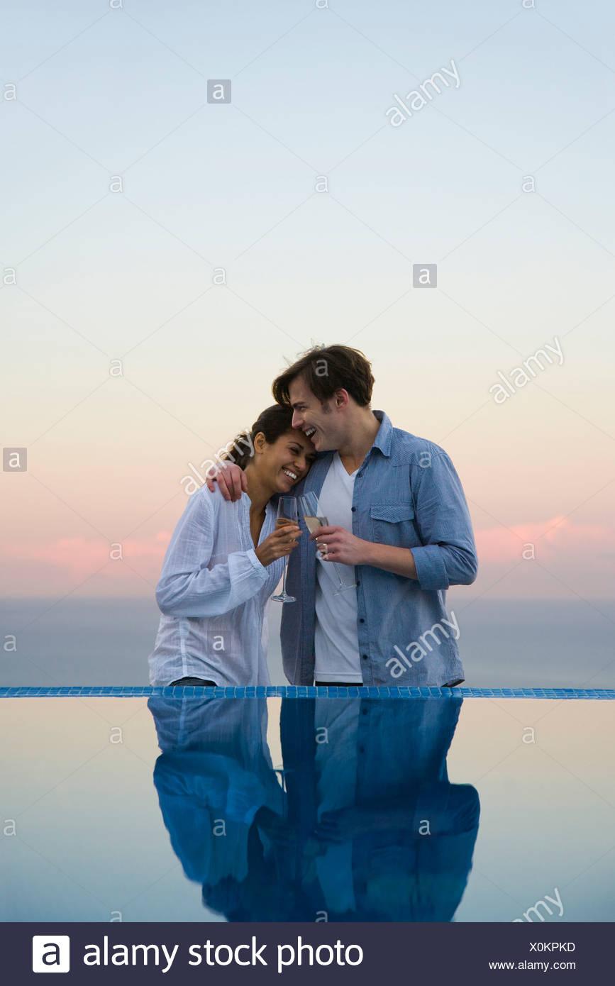 Couple embracing at edge of infinity pool, enjoying champagne - Stock Image