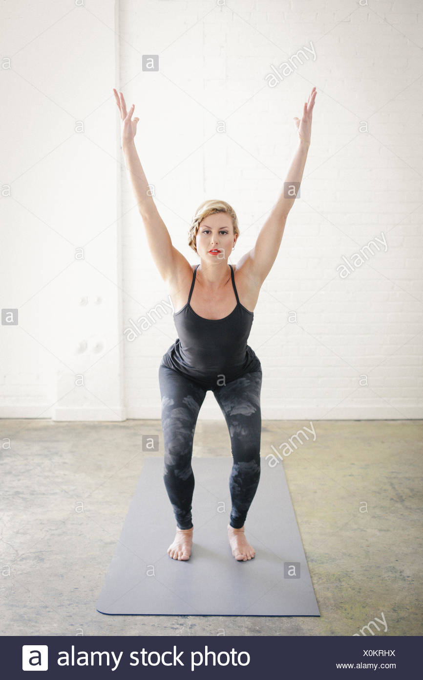 A blonde woman on a yoga mat in a room, doing yoga, squatting down with her arms raised. - Stock Image