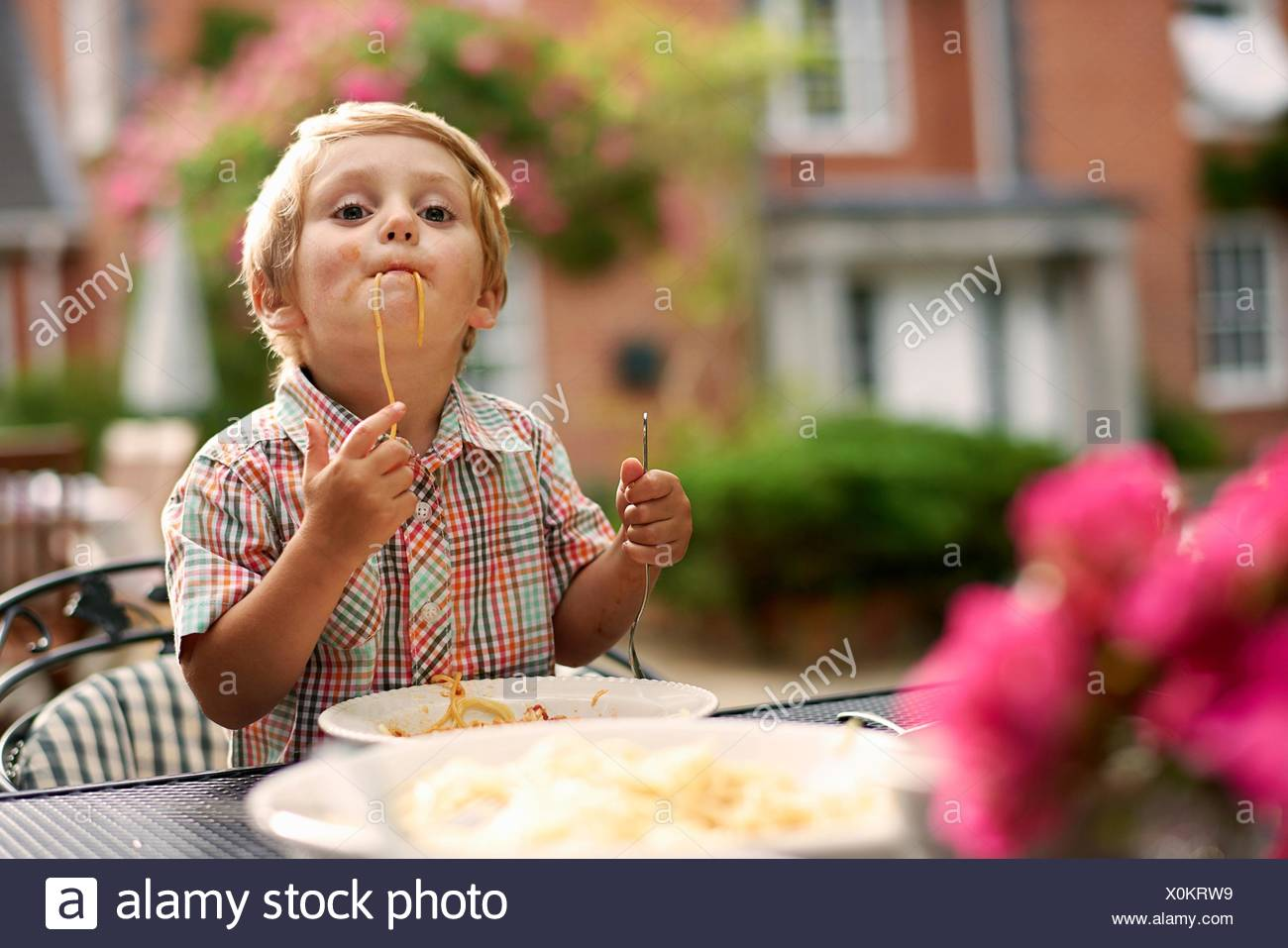 Boy sitting at garden table sucking up spaghetti looking at camera - Stock Image