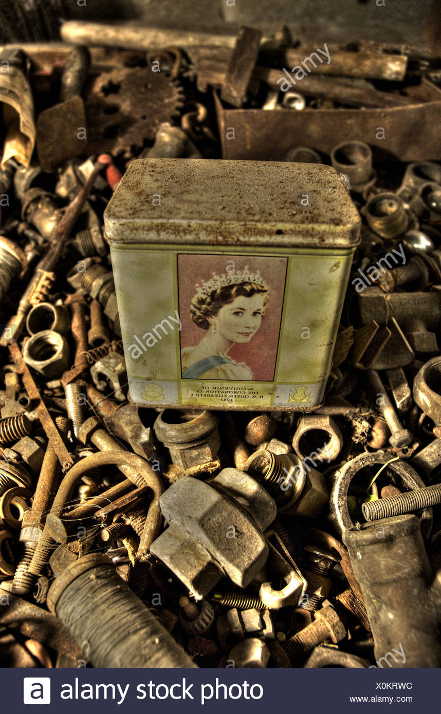 An old tin with a picture of Queen Elizabeth II in a box of old nuts and bolts Stock Photo