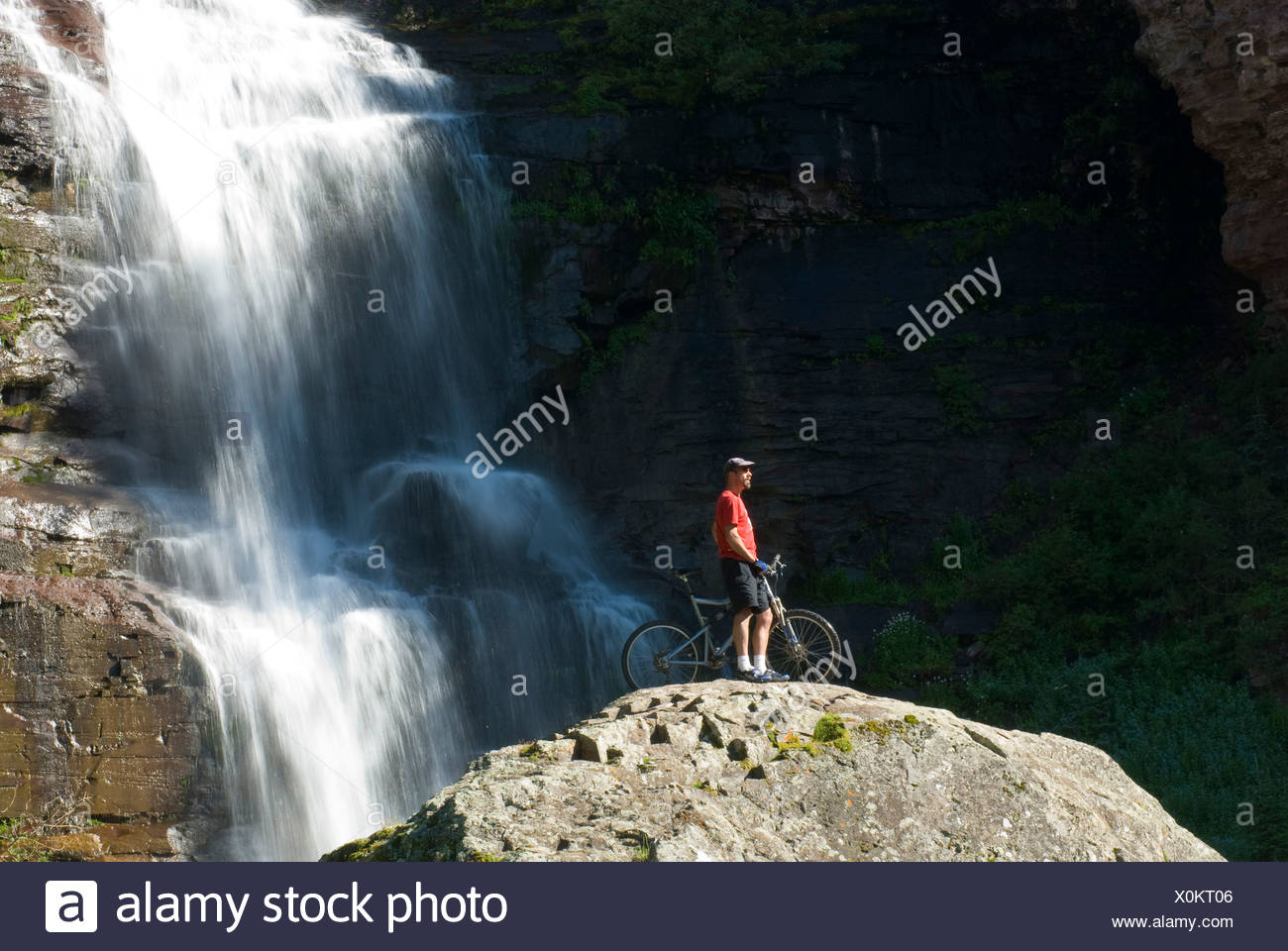 Man and mountain bike on rock, Bear Creek Falls, Telluride, Colorado. - Stock Image
