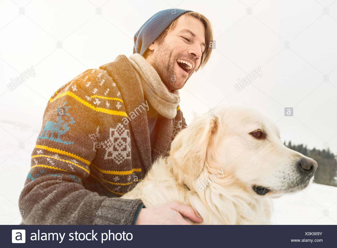 Man wearing knitted cardigan with dog in snow - Stock Image