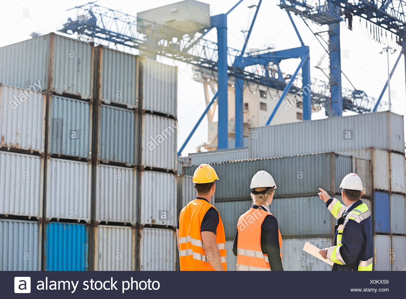 Rear view of workers inspecting cargo containers in shipping yard - Stock Image