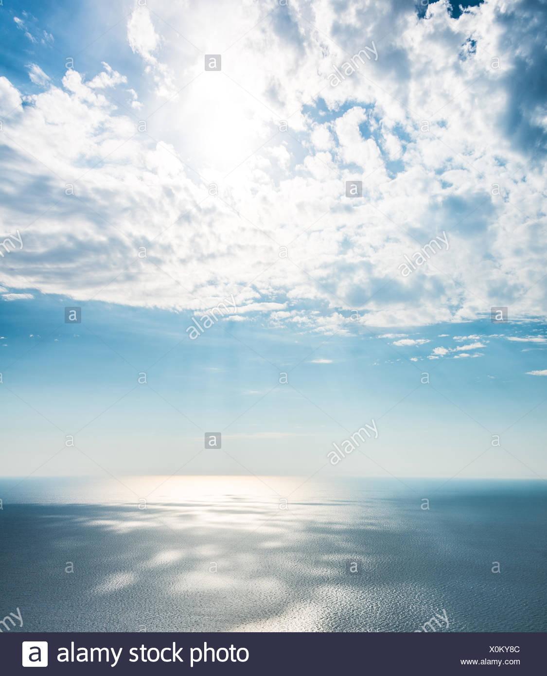 5f87c9e46e0b Sunlight shining through clouds over the sea