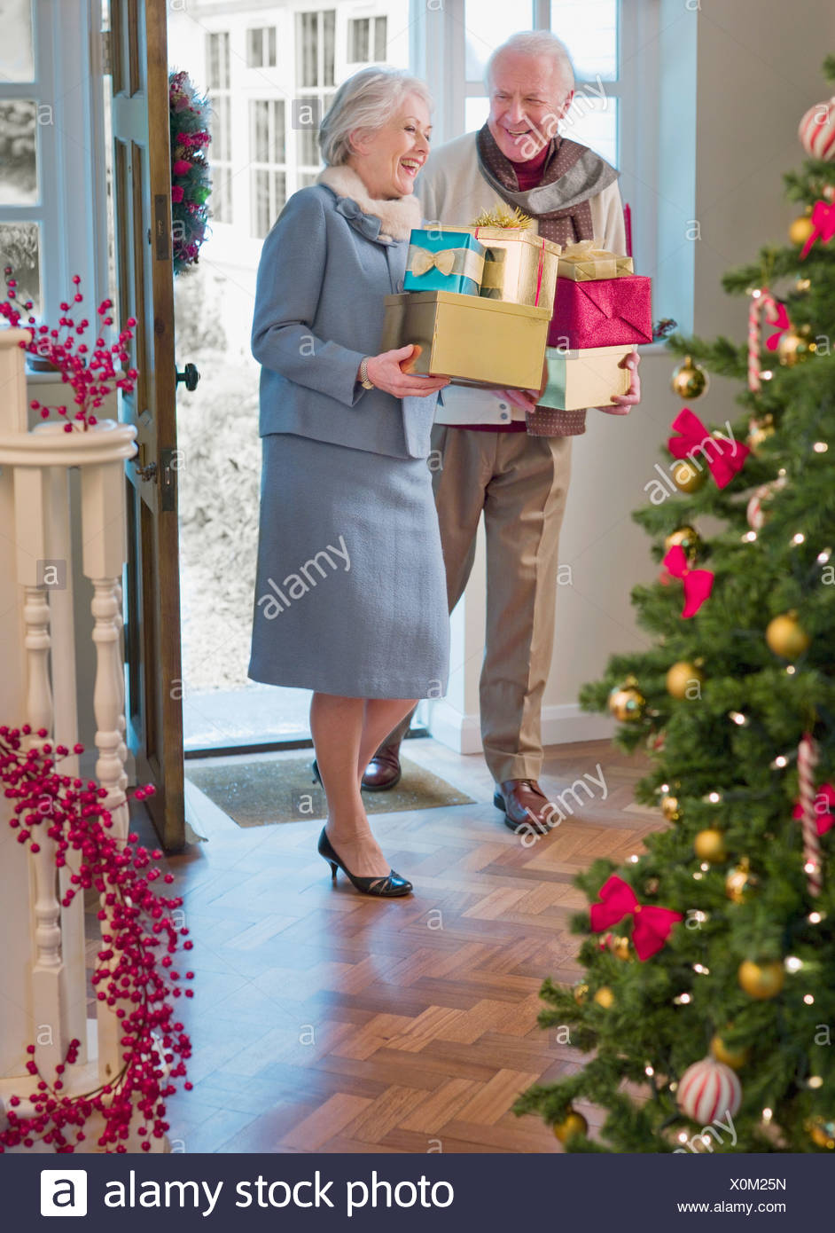 Couple entering house with Christmas gifts Stock Photo