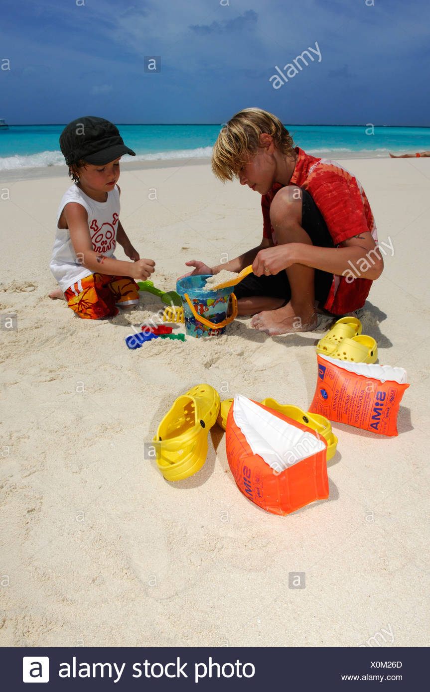 Children playing on the beach in Laguna Resort, The Maldives, Indian Ocean - Stock Image