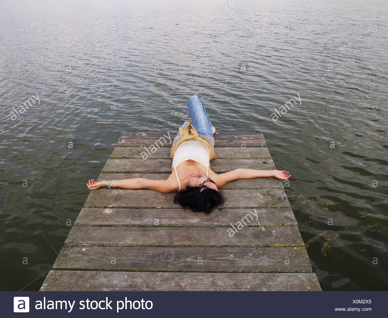 Woman relaxing lying on a wooden pier at a lake, Mecklenburg Lake District, Mecklenburg-Western Pomerania, Germany, Europe - Stock Image