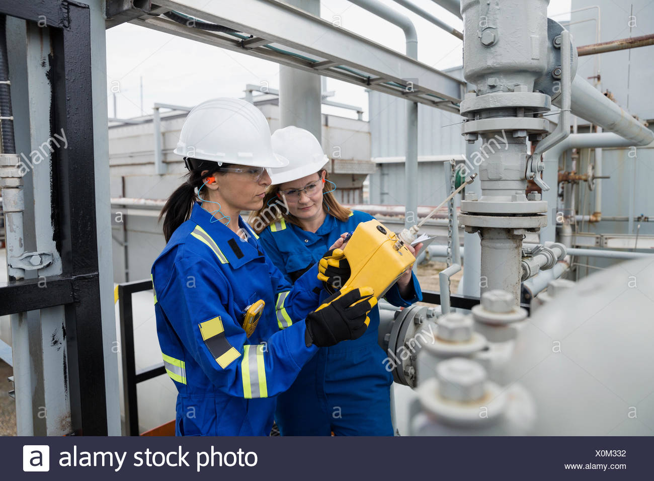 Female workers checking equipment at gas plant - Stock Image