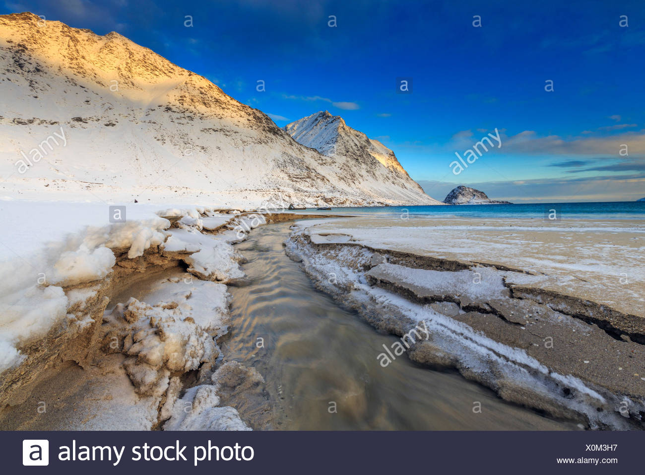 The golden sunrise illuminates the snowy peaks. Haukland Lofoten Islands Norway Europe - Stock Image