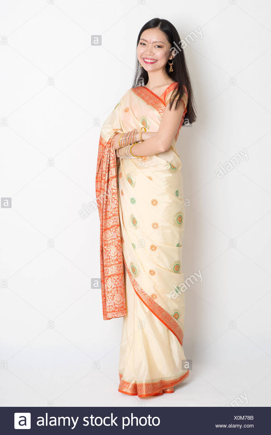 Full length confident fair skin tone Asian Indian female smiling and standing on plain background. - Stock Image